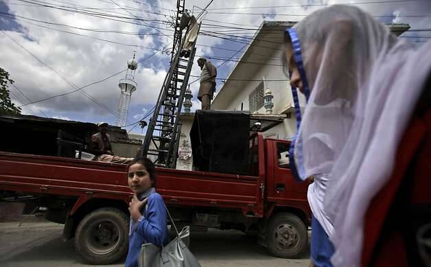 In this Monday, April 30, 2012 photo, Pakistani schoolgirls walk by municipality workers fixing electrical wires in Abbottabad, Pakistan. One year since U.S. commandos flew into this army town and killed Osama bin Laden, Pakistan has tried to close one of the most notorious chapters in its history. The compound that housed him for six years was razed to the ground, and the wives and children who shared the hideaway were flown to Saudi Arabia just last week. (AP Photo/Muhammed Muheisen) Photo: Muhammed Muheisen, Associated Press