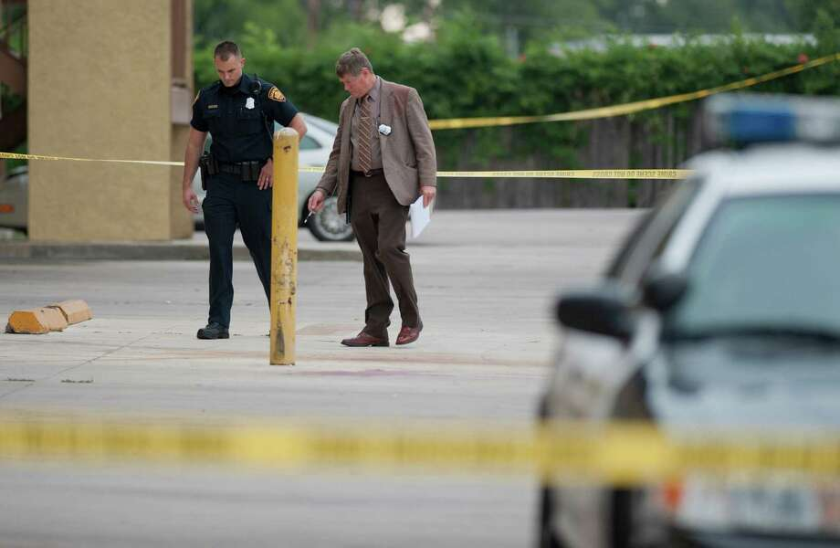 SAPD detective Lon Doyle, right, and an SAPD officer, investigate a stabbing, Wednesday, May 2, 2012, in the 5700 block of Industry Park, near I-35 and Rittiman Rd in San Antonio. The victim was a male in his late twenties, who was taken to hospital in unknown condition, Doyle said. Photo: Darren Abate, Darren Abate/Special To The Express-News