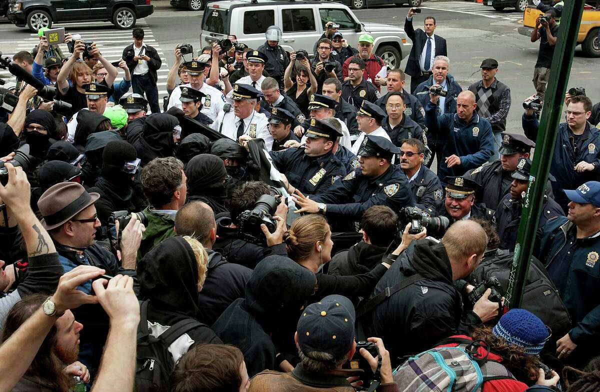 New York Police Department (NYPD) officers clash with demonstrators affiliated with the Occupy Wall Street movement protest in New York, U.S., on Tuesday, May 1, 2012. Occupy Wall Street demonstrators, whose anti-greed message spread worldwide during an eight-week encampment in Lower Manhattan last year, plan marches across the globe today calling attention to what they say are abuses of power and wealth. Photographer: Scott Eells/Bloomberg