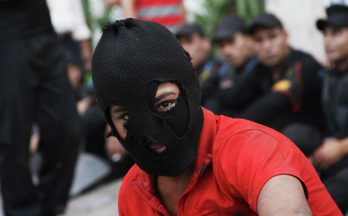An Egyptian protester attends a demonstration outside the Defense Ministry in Cairo, Egypt, Wednesday, May 2, 2012. Suspected supporters of Egypt's military rulers attacked predominantly Islamist anti-government protesters outside the Defense Ministry in Cairo Wednesday, setting off clashes that left more than ten people dead as political tensions rise three weeks before crucial presidential elections. Egyptian police officers are seen, background.