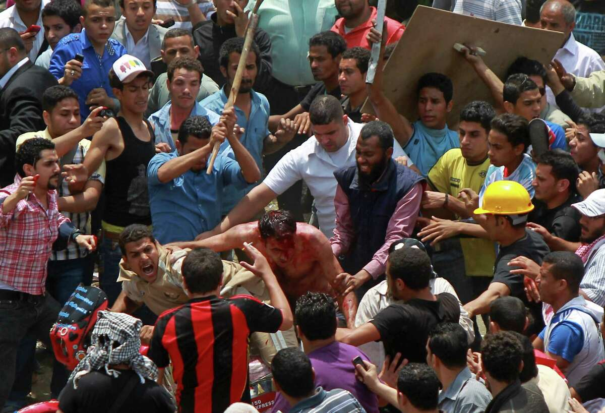 TOPSHOTS Egyptian protesters beat a man (C) who they accused of attacking them in the Abbassiya district in Cairo on May 2, 2012. At least 12 people were killed when attackers stormed an anti-military protest near the defence ministry in Cairo, medics and a security official said. The fate of the man is unknown. AFP PHOTO/STRSTR/AFP/GettyImages