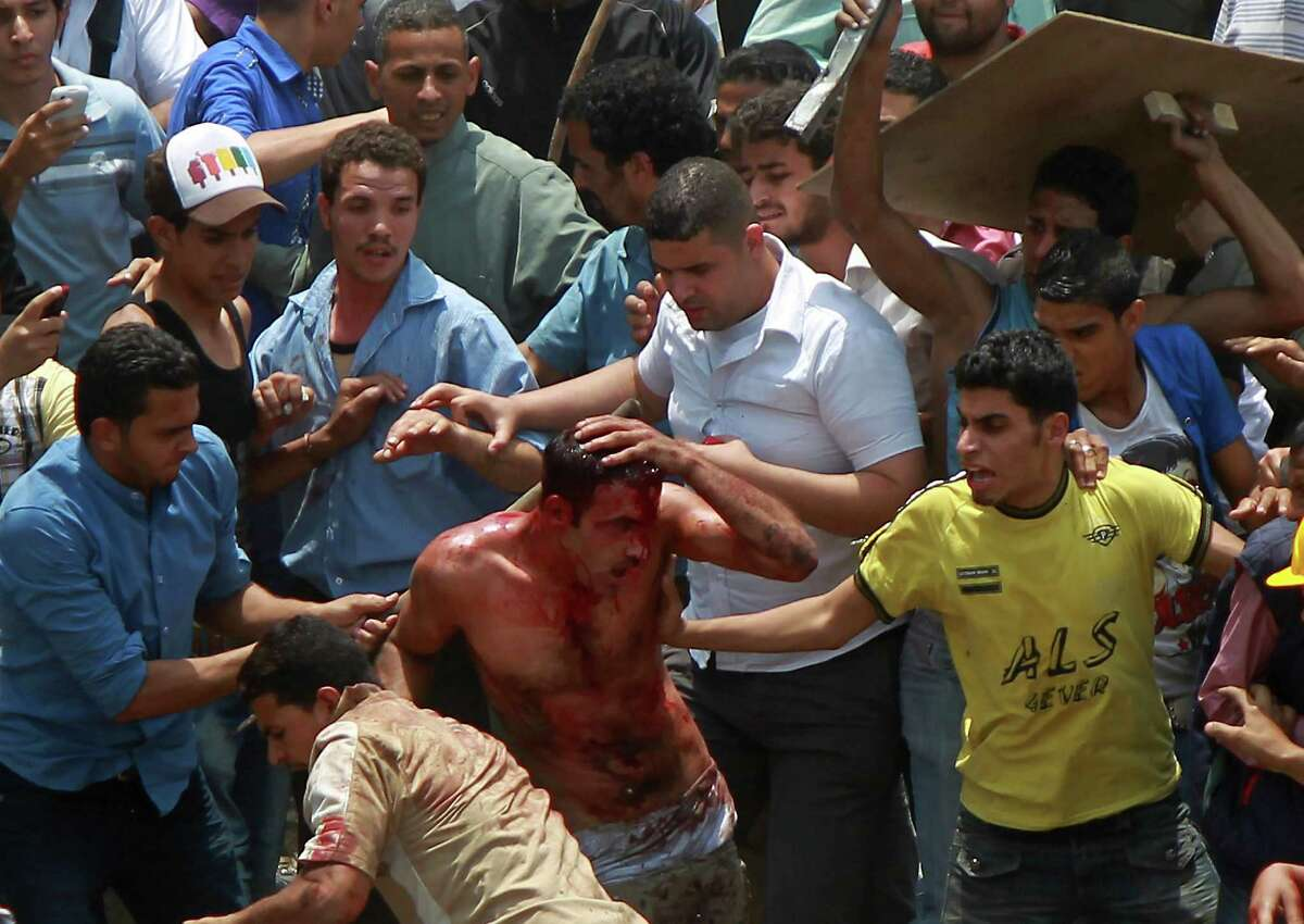 Egyptian protesters beat a man who they accused of attacking them in the Abbassiya district in Cairo on Wednesday. At least 11 people were killed when attackers stormed an anti-military protest near the defense ministry in Cairo, medics and a security official said. The fate of the man is unknown. (STR/AFP/GettyImages)