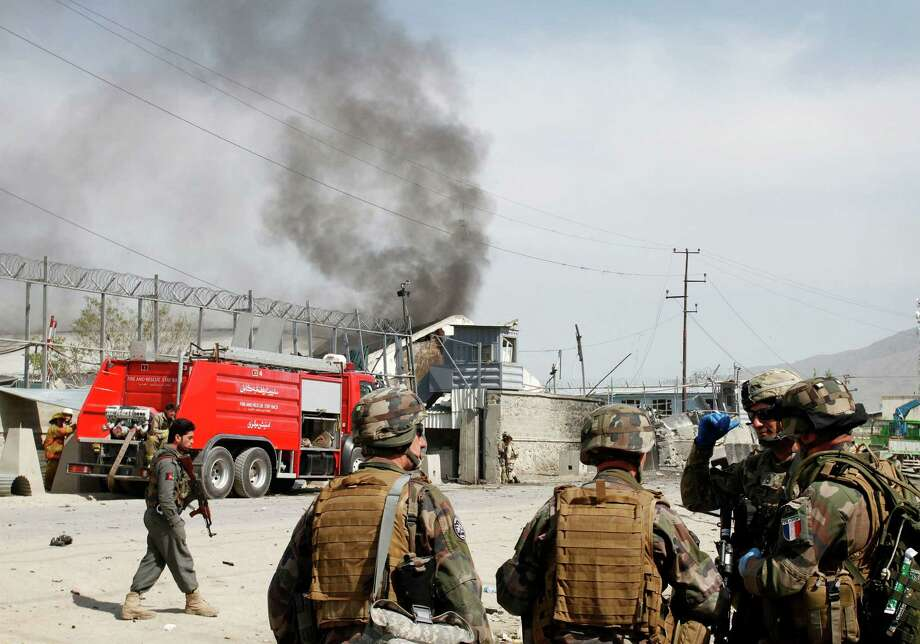 NATO soldiers talk among themselves as smoke comes out of a compound at the scene of militants' attack in Kabul, Afghanistan, Wednesday, May 2, 2012. A suicide car bomber and Taliban militants disguised in burqas attacked the compound housing hundreds of foreigners in the Afghan capital on Wednesday, officials and witnesses said. The Taliban said the attack was a response to U.S. President Barack Obama's surprise visit just hours earlier. (AP Photo/Musadeq Sadeq) Photo: Musadeq Sadeq, Associated Press / AP
