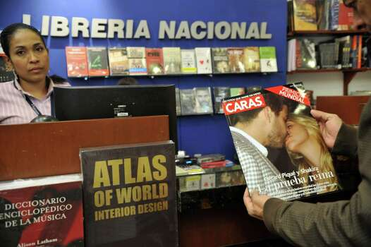 A man has a look at a copy of the latest edition of Colombia's Caras magazine, with a picture of Colombian pop singer and Spanish footballer Gerard Pique kissing, on March 14, 2011, in Bogota, Colombia. Patricia Fajardo, director of the magazine in Colombia, said that photographers contacted them last week offering a package of 15 photos of Shakira and the player of Barcelona at a party the couple held on February 2 in Barcelona, Spain, to celebrate their birthdays, both born on that date though with a difference of ten years. AFP PHOTO/GUILLERMO LEGARIA Photo: GUILLERMO LEGARIA, AFP/Getty Images / 2011 AFP