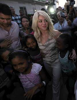 Surrounded by fans, Colombia's singer Shakira, center, leaves after attending the inauguration of a child care center in Cartagena, Colombia, Thursday, April 12, 2012. Shakira will sing the National Anthem of Colombia during the opening ceremony of the 6th Summit of the Americas in Cartagena on April 14. Photo: AP