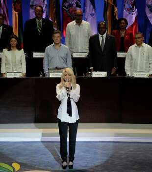 Heads of State stand at attention in the back as Colombia's pop star Shakira sings her country's national anthem at the opening ceremony of the sixth Summit of the Americas at the Convention Center in Cartagena, Colombia, Saturday April 14, 2012. The summit brings together presidents and prime ministers from Canada, the Caribbean, Latin America and the U.S. Photo: AP
