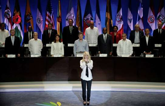 Colombia's pop star Shakira sings her country's national anthem backdropped by leaders of the Western Hemisphere at the opening ceremony of the sixth Summit of the Americas in Cartagena, Colombia, Saturday April 14, 2012. The summit brings together presidents and prime ministers from Canada, the Caribbean, Latin America and the U.S. Photo: AP