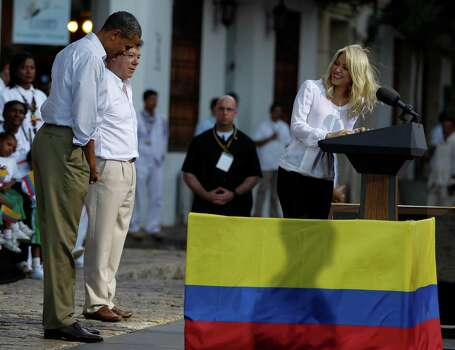 President Barack Obama, left, gestures to Colombia's pop star Shakira, right, as Colombia's President Juan Manuel Santos looks on during a  land titling event for Afro-Colombian communities in Cartagena, Colombia, Sunday April 15, 2012. Photo: AP