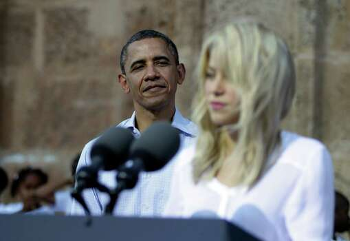 President Barack Obama, left, listens to Colombian singer Shakira during a land titling event for Afro-Colombian communities in Cartagena, Colombia, Sunday, April 15, 2012. Photo: AP