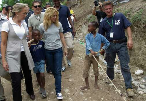 ADVANCE FOR USE SUNDAY, APRIL 22, 2012 AND THEREAFTER - FILE - In this Sunday, April 11, 2010 file photo, Colombian singer Shakira, center left, and U.S. actor Sean Penn, right, walk with children during a visit to the makeshift camp in the Petionville Golf Club in Port-au-Prince, Haiti. The actor who stormed onto the scene of one of the worst natural disasters in history two years ago has certainly not lost interest. Defying skeptics, he has put down roots in Haiti, a country he hadn't even visited before the January 2010 earthquake, and has become a major figure in the effort to rebuild. Photo: AP