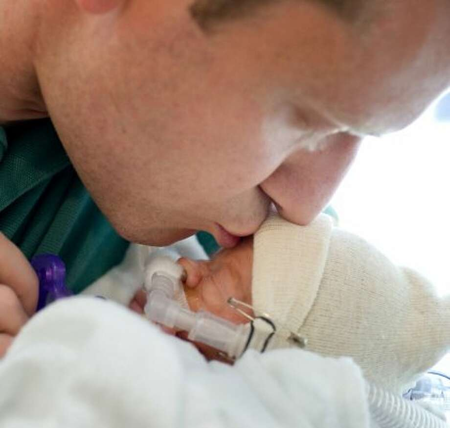 Dad David Perkins kisses one of his new babies. (A. Kramer / Texas Childrens Hospital)