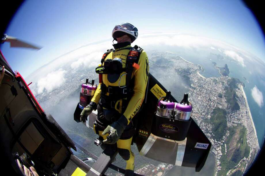 In this photograph provided by the Breitling, Yves Rossy, known as the Jetman, jumps from a helicopter over Rio de Janiero, Brazil, Wednesday, May 2, 2012. The Swiss aviator dropped from the helicopter and deployed the Jet powered carbon-kevlar Jetwing, which he uses his body to steer, as he flew over the city before landing on Copacabana beach. (AP Photo/Joe Parker, Breitling) Photo: Joe Parker, Associated Press / BREITLING