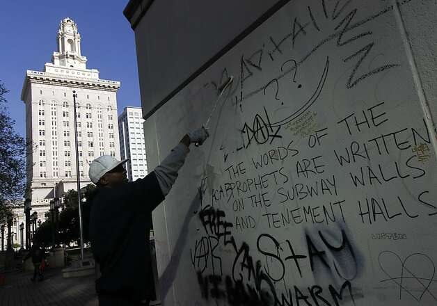 Dion Murphy covers graffiti in front of City Hall in Oakland, Calif. on Wednesday, May 2, 2012, which was left behind by demonstrators during yesterday's protests, many of which turned violent. Photo: Paul Chinn, The Chronicle