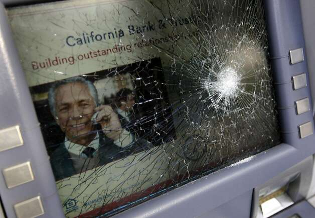 The glass of an ATM remains broken, but the machine works, at the California Bank and Trust branch at 20th and Franklin streets in Oakland, Calif. on Wednesday, May 2, 2012, after yesterday's protests. Photo: Paul Chinn, The Chronicle