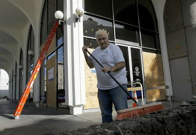 Gary Davis sweeps a wall after a cleanup crew repaired broken windows at the California Bank & Trust branch at 20th and Franklin streets in Oakland, Calif. on Wednesday, May 2, 2012, after yesterday's protests. Photo: Paul Chinn, The Chronicle