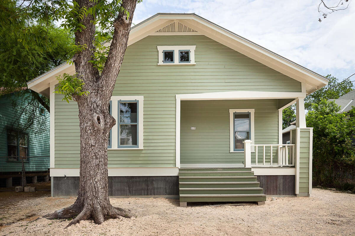 The exterior of this 888-square-foot house has six different types of reclaimed siding, custom storm windows, a metal roof and a skirt built from the original roof. The house has been lifted almost 3 feet from its original position to aid the remodeling process.