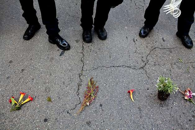 A protester placed flowers at the feet of a police skirmish line during a May Day rally at Frank Ogawa Plaza May 1, 2012, in Oakland, Calif. Photo: Jason Henry, Special To The Chronicle