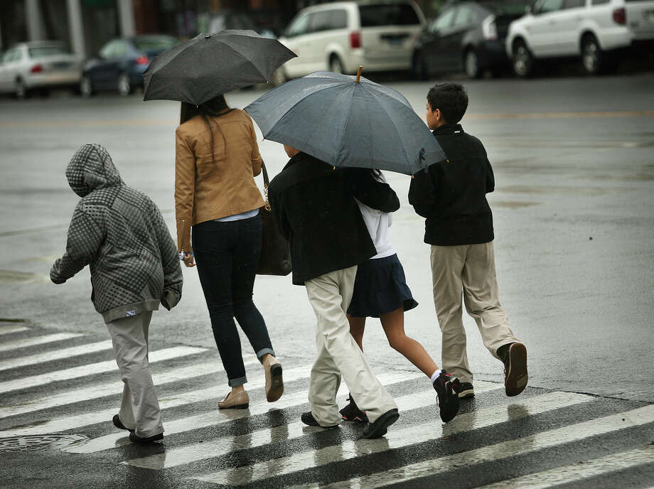 Pedestrians try to stay dry as they cross Reef Road in the rain in downtown Fairfield on Wednesday, May 2, 2012. Photo: Brian A. Pounds / Connecticut Post