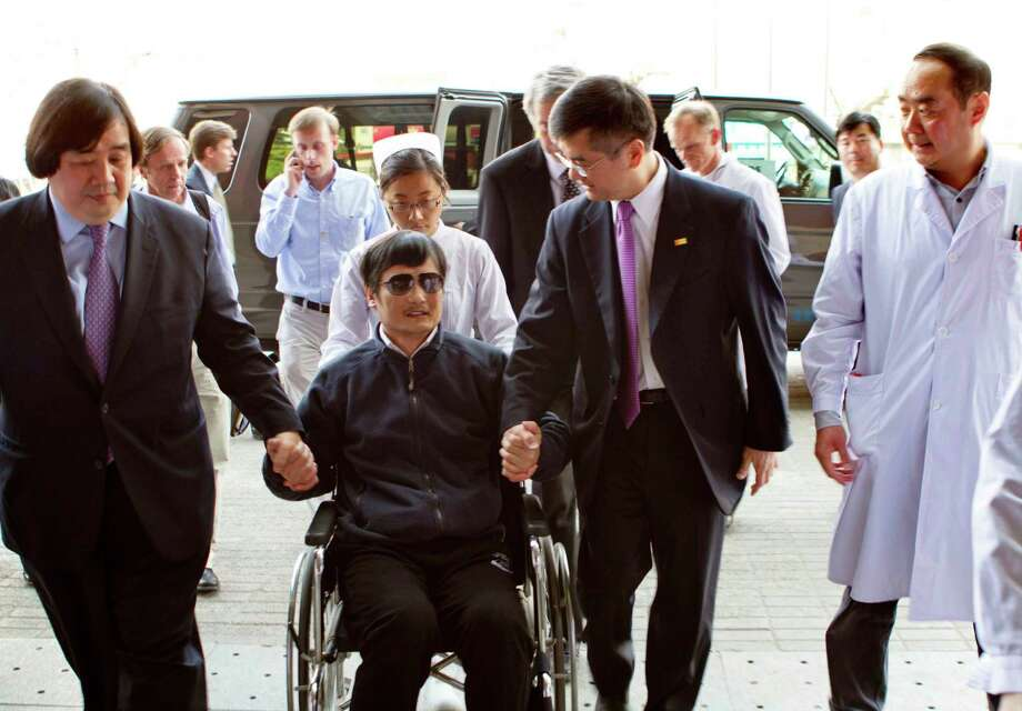 ADDS U.S. STATE DEPARTMENT LEGAL ADVISOR HAROLD KOH AT LEFT   In this photo released by the US Embassy Beijing Press Office, blind lawyer Chen Guangcheng is wheeled into a hospital by U.S. Ambassador to China Gary Locke, right, and an unidentified official at left, in Beijing Wednesday May 2, 2012. At left is U.S. State Department Legal Advisor Harold Koh. Photo: AP / US Embassy Beijing Press Office