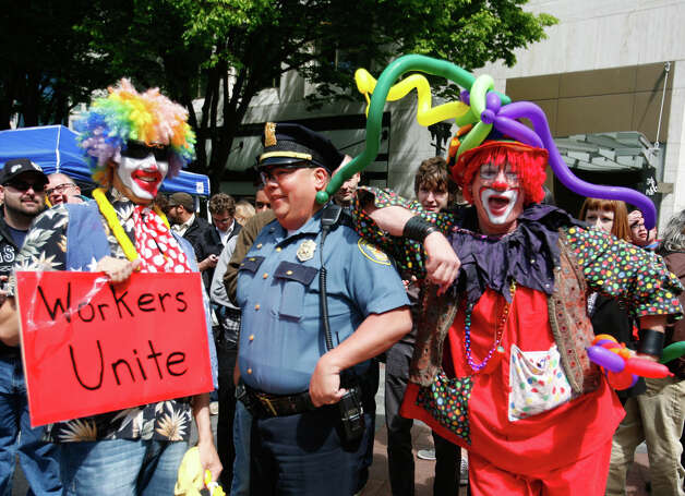May Day  participants pose next to a policeman in Westlake Park. Photo: SOFIA JARAMILLO / SEATTLEPI.COM