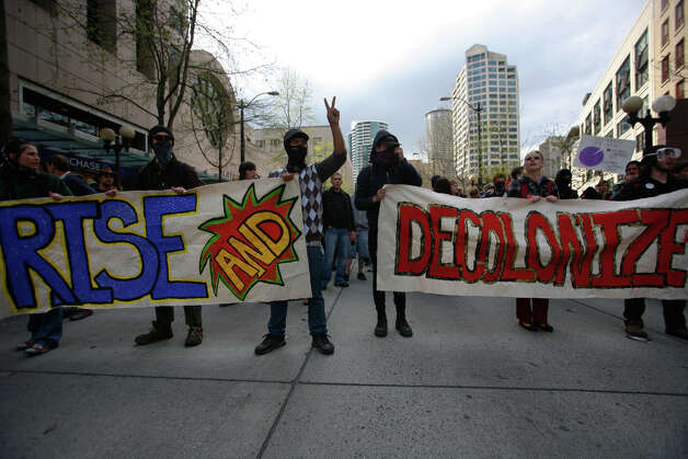 Protestors hold signs during a May Day march in downtown Seattle on Tuesday, May 1, 2012. Photo: SOFIA JARAMILLO / SEATTLEPI.COM