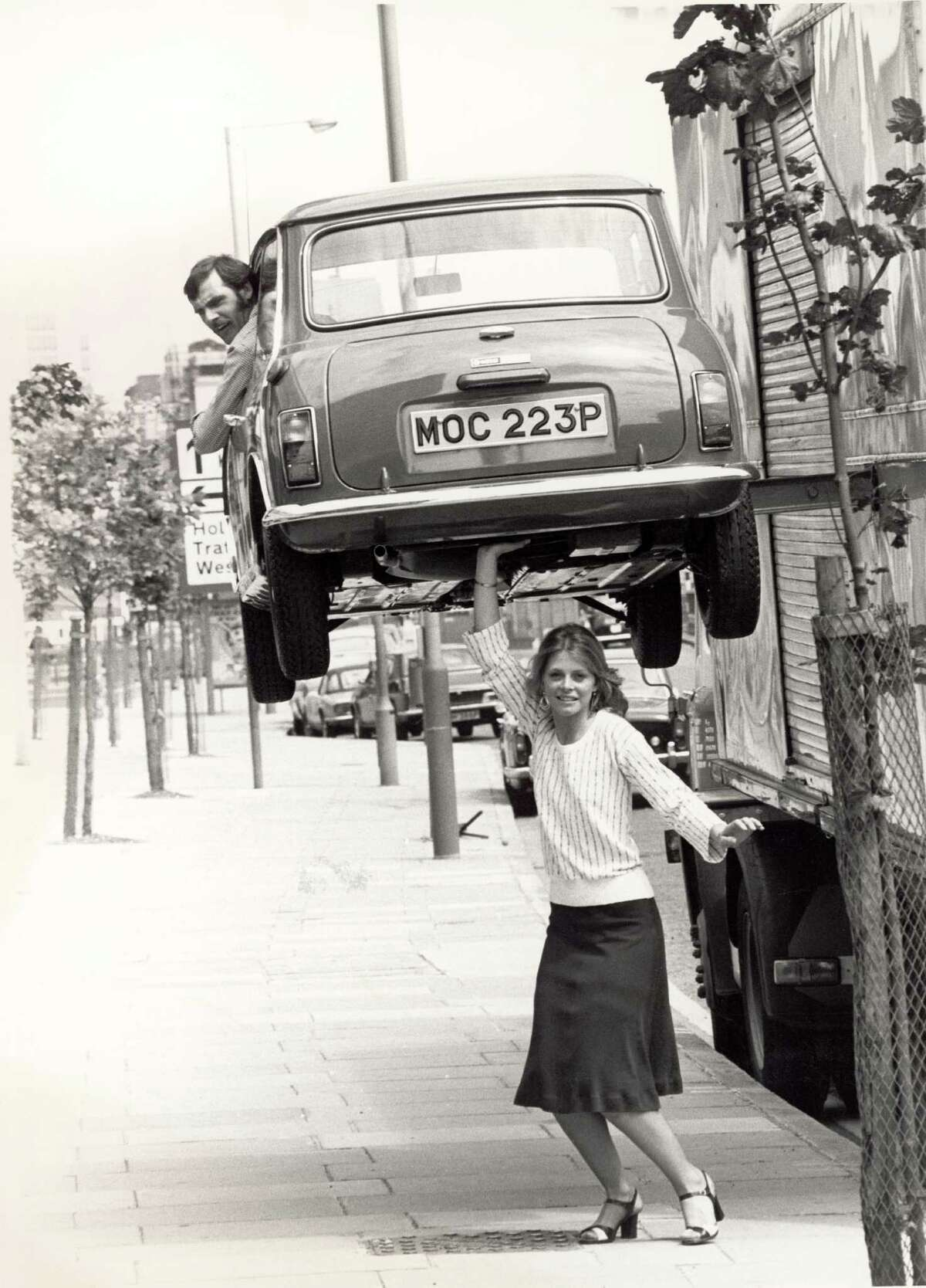 Superheroine portrayals go back a long way, thanks to TV. Here, Lindsay Wagner appears to hold a man in a car above her head during a visit to London to promote the television series 'The Bionic Woman,