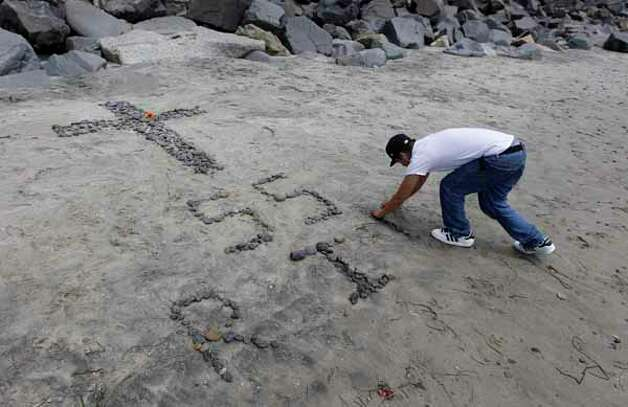 Jimmy Garcia constructs a make-shift memorial on the beach near the home of former NFL star Junior Seau in Oceanside, Calif., Wednesday, May 2, 2012. Seau was found shot to death at his home Wednesday morning in what police said appeared to be a suicide. He was 43. Photo: Chris Carlson, . / AP