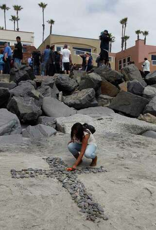 A mourner grieves at a make-shift memorial on the beach near the home of former NFL star Junior Seau in Oceanside, Calif., Wednesday, May 2, 2012. Seau was found shot to death at his home Wednesday morning in what police said appeared to be a suicide. He was 43. Photo: Chris Carlson, . / AP