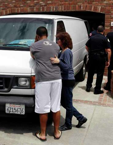 A grieving man is comforted near the van where the body of former NFL star Junior Seau was loaded in to, Wednesday, May 2, 2012, in Oceanside, Calif. Seau was found shot to death at his home Wednesday morning in what police said appeared to be a suicide. He was 43. Photo: Chris Carlson, . / AP