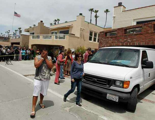 A grieving man walks past a van where the body of former NFL star Junior Seau was loaded in Oceanside, Calif., Wednesday, May 2, 2012. Seau was found shot to death at his home Wednesday morning in what police said appeared to be a suicide. He was 43. Photo: Chris Carlson, . / AP