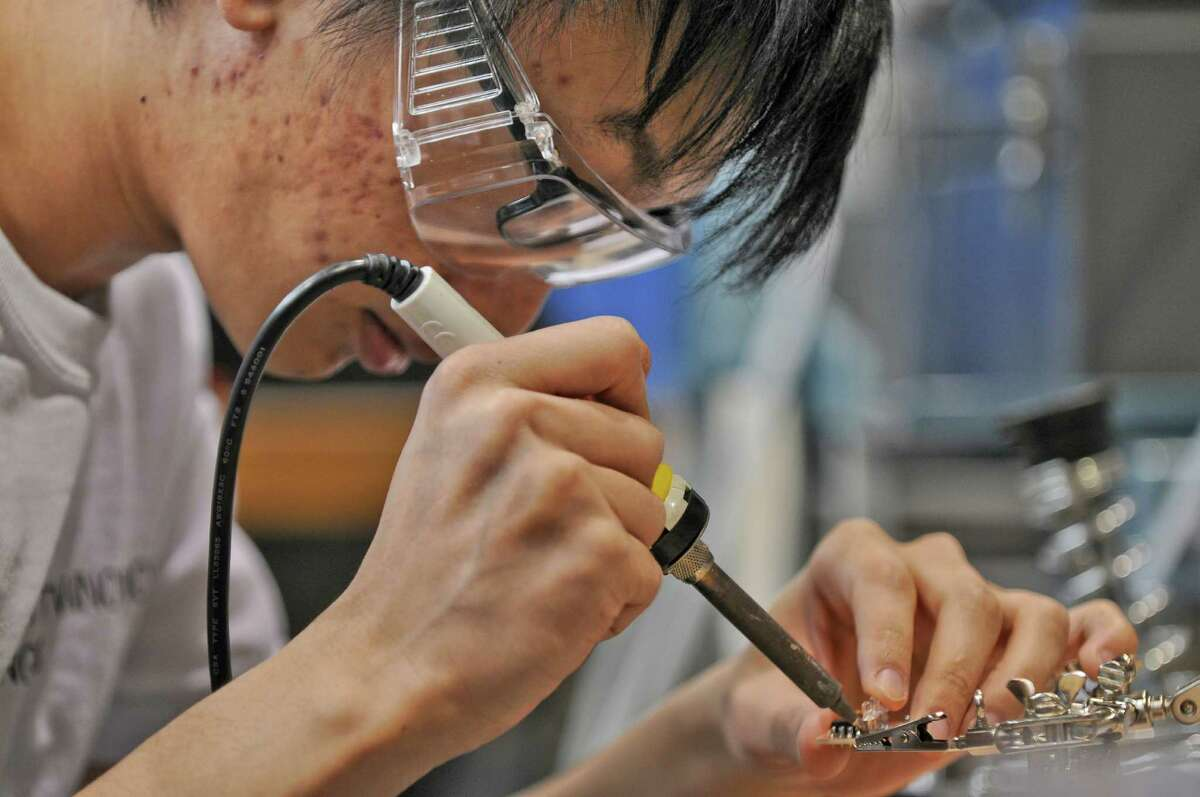 RPI senior Ben Gao of Brooklyn works on a circuit board for a bicycle headlight that he and fellow students made through a project they implemented to build a manufacturing system to produce and assemble 400 headlights, in RPI's Manufacturing Innovation Learning Lab, on Wednesday May 2, 2012 in Troy, NY. (Philip Kamrass / Times Union )