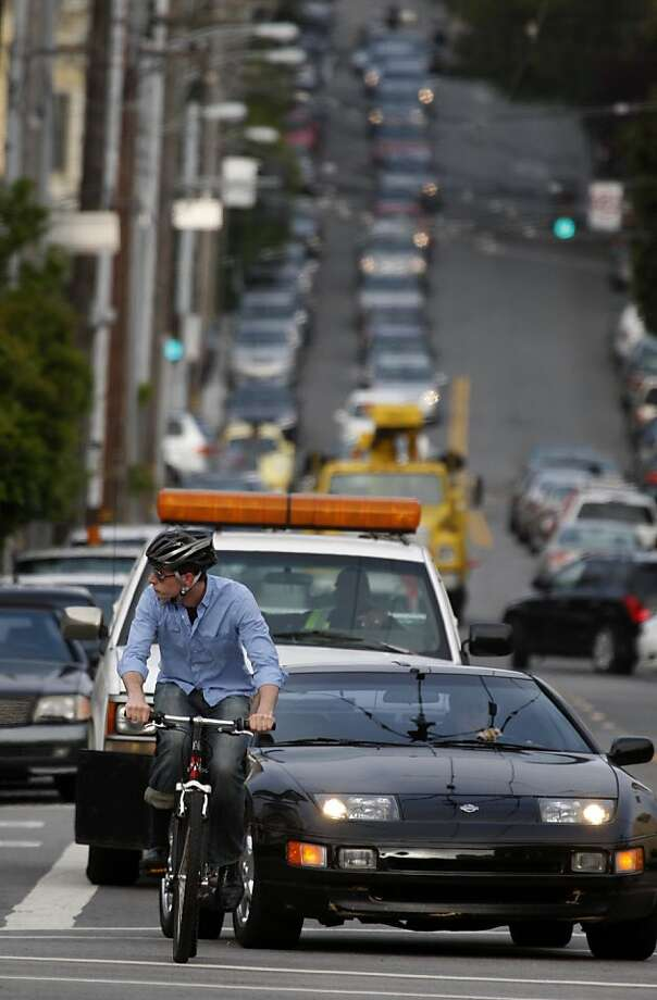 A bicyclist checks for oncoming traffic while merging onto Market Street from Page Street on Bike to Work Day in San Francisco, Calif., on Thursday, May 13, 2010. Photo: Paul Chinn, The Chronicle