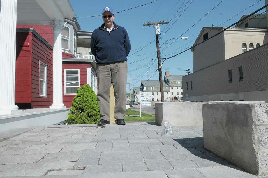 Anthony Alfonso on his stone landing in front of his home near the College of Saint Rose on Thrusday, April 26, 2012 in Albany, NY.  Anthony and his wife Ali Alfonzo say their home was damaged during the construction of a College of Saint Rose dorm. The Alfonsos say pavers in part of the landing have sunk.  (Paul Buckowski / Times Union) Photo: Paul Buckowski