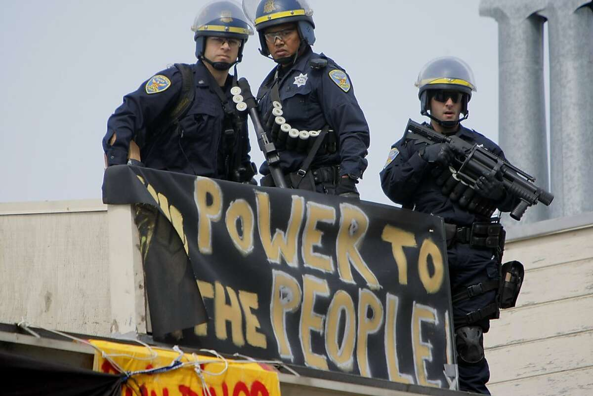 San Francisco police officers keep watch on protesters after police moved in to evict dozens of people that took over a building at the corner of Gough and Turk Streets on April, 2, 2012.
