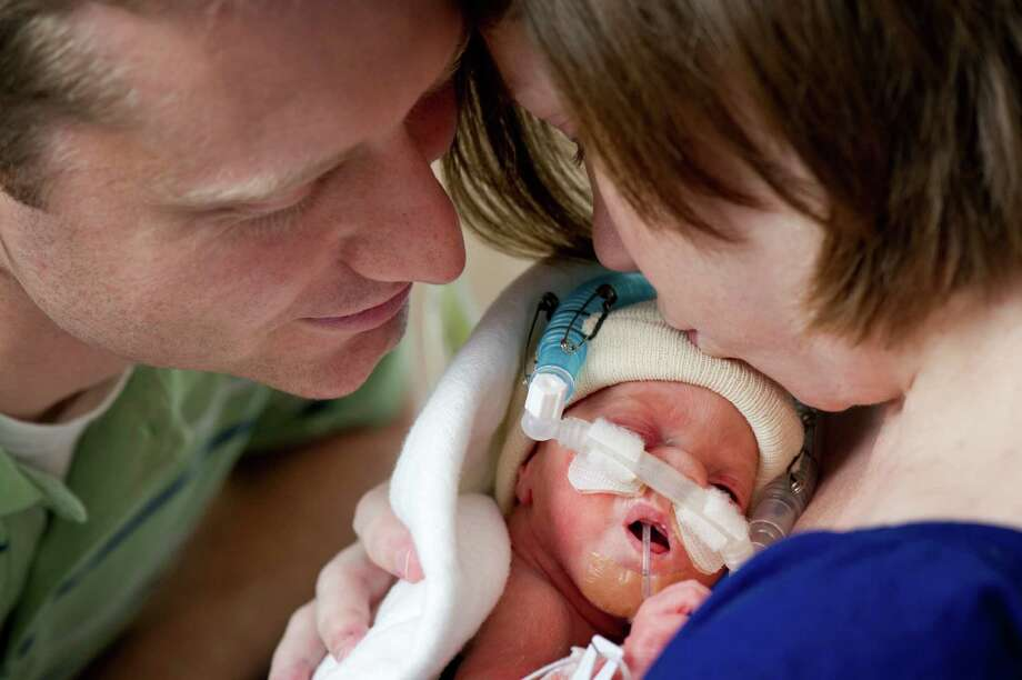 """""""We're ordinary people entrusted by God with an extraordinary responsibility,"""" said David Perkins, shown with Lauren and daughter Caroline at Texas Children's Hospital."""