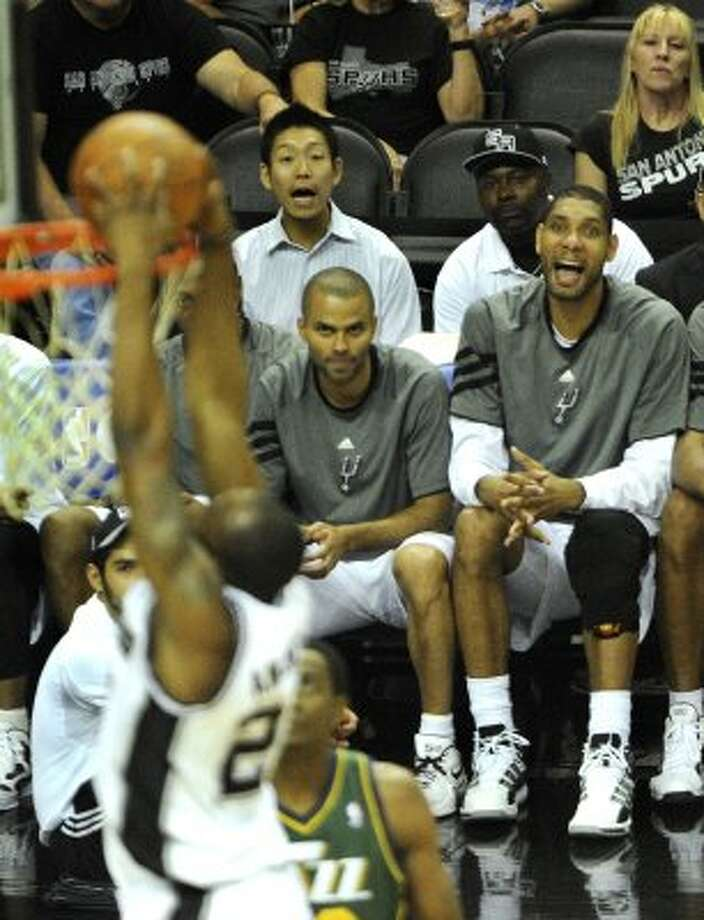 Tony Parker, left, and Tim Duncan of the Spurs watch from the bench as teammate James Anderson dunks during fourth-quarter action of the Spurs 114-83 victory over the Jazz in NBA playoffs action at the AT&T Center on Wednesday, May 2, 2012.  Billy Calzada / San Antonio Express-News (BILLY CALZADA / San Antonio Express-News)
