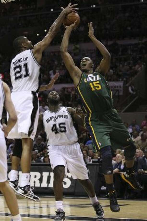 The Spurs'  Tim Ducan blocks a shot by the Jazz's Derrick Favors but is called for a foul during the second half of game two of the Western Conference first round at the AT&T Center, Sunday, May 2, 2012. The Spurs won 114-83 and lead the series, 2-0. Jerry Lara/San Antonio Express-News (Jerry Lara / San Antonio Express-News)