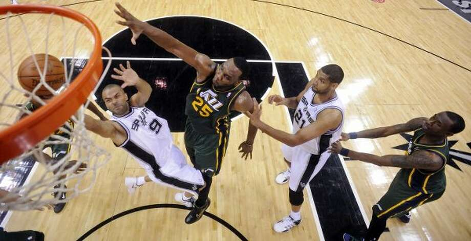 The Spurs'  Tony Parker shoots around the Jazz's Al Jefferson as the Spurs's Tim Duncan and Jazz's Josh Howard look on during first half action of Game 2 of the Western Conference first round Wednesday May 2, 2012 at the AT&T Center. The Spurs won 114-83.  EDWARD A. ORNELAS/SAN ANTONIO EXPRESS-NEWS (EDWARD A. ORNELAS / SAN ANTONIO EXPRESS-NEWS)
