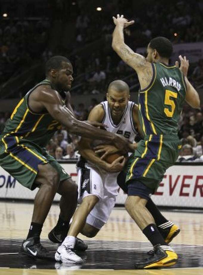 The Spurs'  Tony Parker drives through the Jazz's Paul Millsap, left, and Devin Harris during the first half of game two of the Western Conference first round at the AT&T Center, Sunday, May 2, 2012. Jerry Lara/San Antonio Express-News (Jerry Lara / San Antonio Express-News)