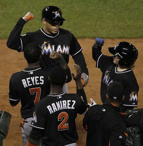 Miami Marlins' Giancarlo Stanton, top, is congratulated after hitting a solo home run off of San Francisco Giants pitcher Santiago Casilla during the tenth inning of a baseball game in San Francisco, Wednesday, May 2, 2012. (AP Photo/Jeff Chiu) Photo: Jeff Chiu, Associated Press