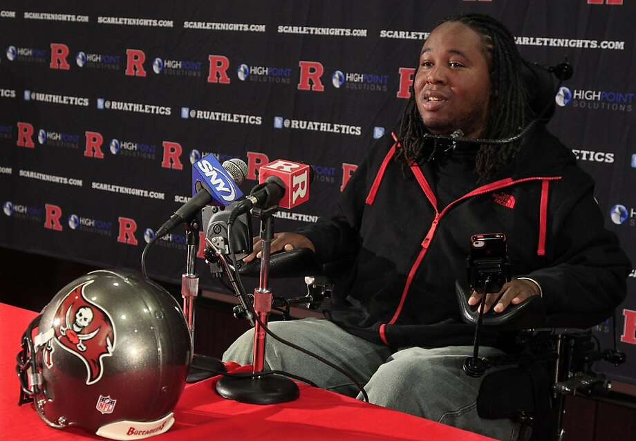 Paralyzed former Rutgers football player Eric LeGrand answers a question while sitting near a Tampa Bay Buccaneers helmet in Piscataway, N.J., Wednesday, May 2, 2012, after it was announced that he has been signed by the Buccaneers. LeGrand broke two vertebrae and suffered a serious spinal cord injury on Oct. 16, 2010 during a kickoff return against Army. His coach at Rutgers then, Greg Schiano, now is coach of the Bucs. (AP Photo/Mel Evans) Photo: Mel Evans, Associated Press