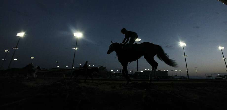 Horses workout before the sun come up at Churchill Downs Wednesday, May 2, 2012, in Louisville, Ky. (AP Photo/Charlie Riedel) Photo: Charlie Riedel, Associated Press