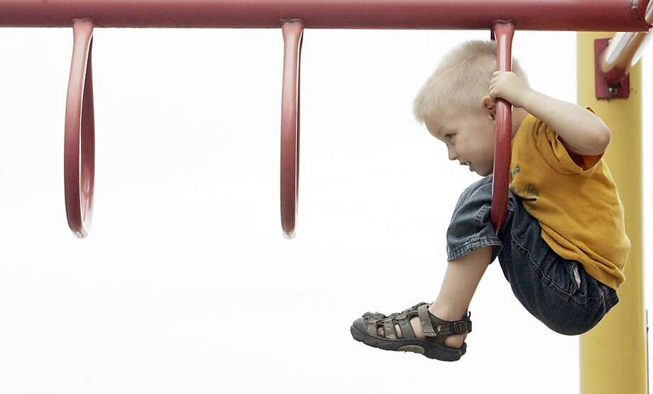 Defeated by the monkey bars:Unable to continue any farther, 3-year-old Daniel Kniola Jr. calls out to Mom in LaPorte, Ind. Photo: Bob Wellinski, Associated Press