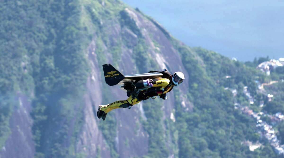 Yves Rossy, known as the Jetman, flies over Corcovado Mountain during a successful flight over Rio de Janiero, Brazil, on Wednesday The Swiss aviator dropped from a helicopter and deployed the Jet powered carbon-kevlar Jetwing which he uses his body to steer as he flew over the city before landing on Copacabana Beach. (John Parker/Breitling via AP Images)