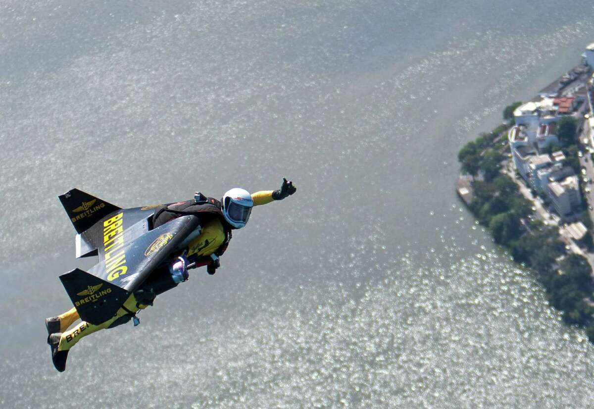 In this photograph provided by the Breitling, Yves Rossy, known as the Jetman, flies over Rio de Janiero, Brazil, Wednesday. The Swiss aviator dropped from a helicopter and deployed the jet powered carbon-kevlar Jetwing, which he uses his body to steer, as he flew over Rio before landing on Copacabana beach. (AP Photo/John Parker, Breitling)