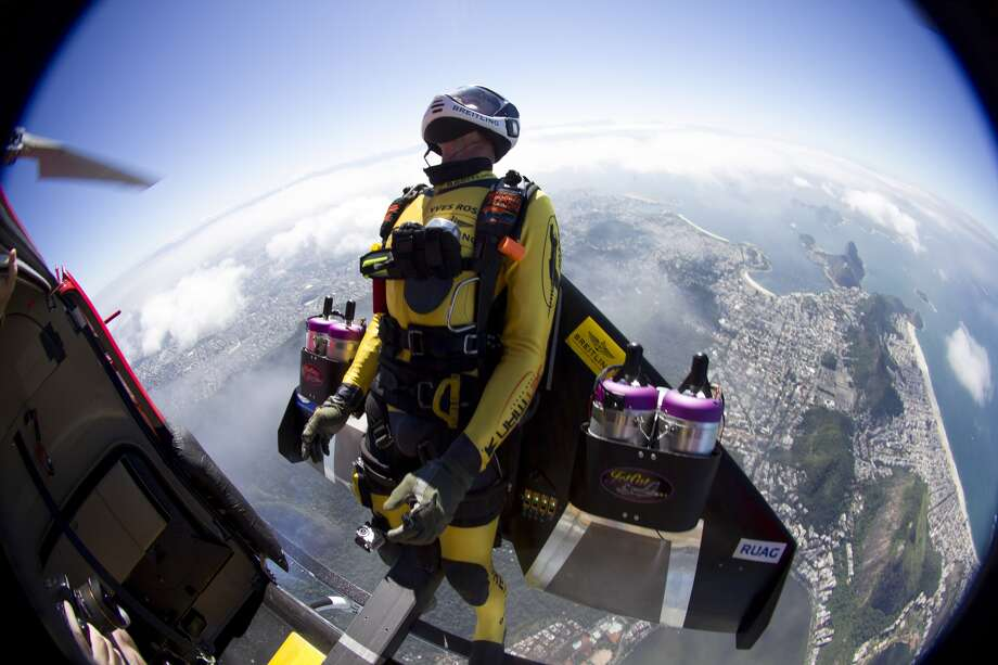 In this photograph provided by the Breitling, Yves Rossy, known as the Jetman, jumps from a helicopter over Rio de Janiero, Brazil, Wednesday. The Swiss aviator dropped from the helicopter and deployed the Jet powered carbon-kevlar Jetwing, which he uses his body to steer, as he flew over the city before landing on Copacabana beach. (AP Photo/Bruno Brokken, Breitling)