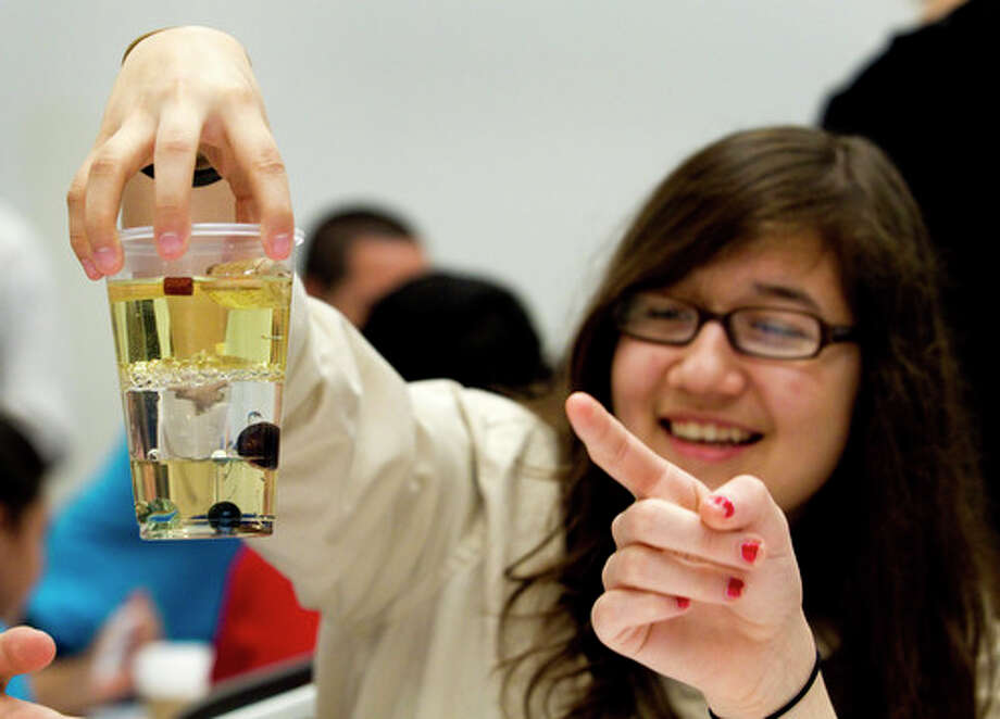 Melanie Rivera, of Klein Forest High School, looks at a cup filled with corn syrup, water and vegetable oil, while conducting an experiment on density during the 2012 Offshore Technology Conference Thursday, May 3, 2012, in Houston. 200 high school students were invited to the OTC to promote students' interest in energy careers. Photo: Brett Coomer, Houston Chronicle / © 2012 Houston Chronicle