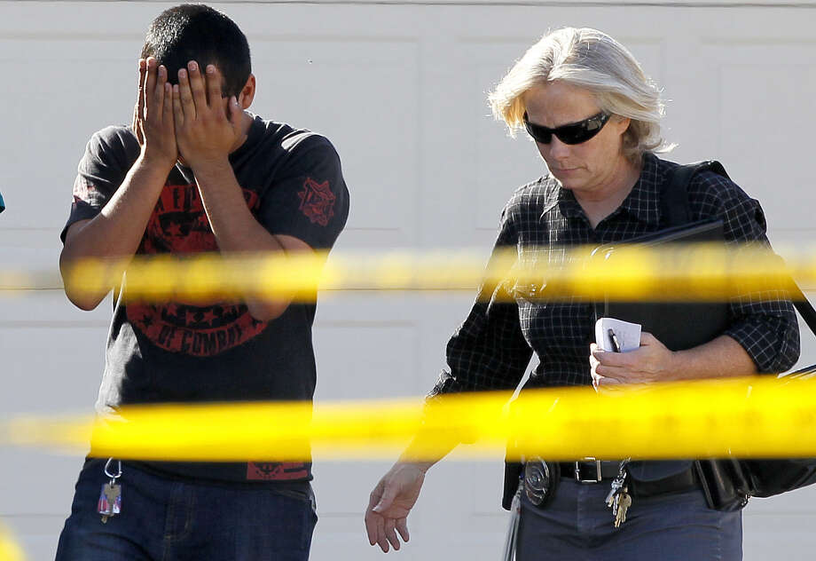 A police officer walks with a man who said he had a child inside of the home where five people were shot Wednesday, May 2, 2012 in Gilbert, Ariz.   Police have identified one of the five people killed in a shooting in a Phoenix suburb as a former Marine with ties to new-Nazi and Minutemen groups. Photo: AP