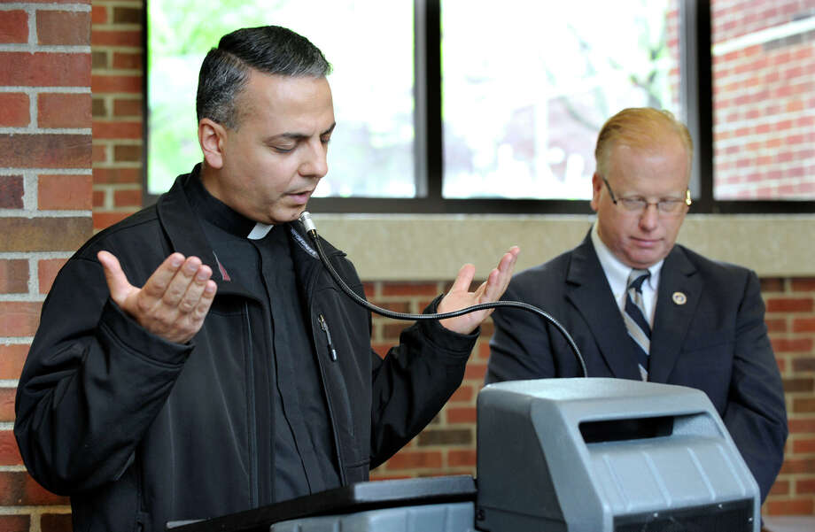 Fr. Jean Younes, pastor of St. Anthony of Padua Church in Danbury, recites the Lord's Prayer in the Aramaic language during an observance of the National Day of Prayer, at Danbury City Hall, Thursday morning, May 3, 2012. At right is Mayor Mark Boughton. Photo: Carol Kaliff / The News-Times