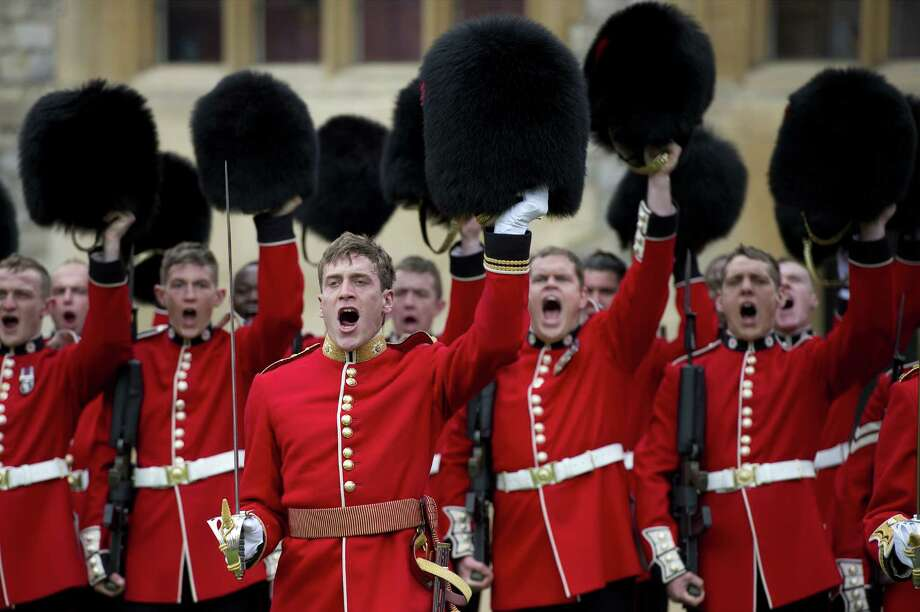 TOPSHOTS British soldiers from the Coldstream Guards remove their headgear in order to honour Britain's Queen Elizabeth II during a ceremony where she presented New Colours to the 1st Battalion and No. 7 Company the Coldstream Guards at Windsor Castle, Berkshire, west of London, on May 3, 2012. The Queen presented New Colours to the 1st Battalion and No. 7 Company of the Coldstream Guards and then inspected the Parade. The Coldstream Guards, the oldest regiment in the British Army, will form part of the guard for Trooping the Colour in honour the the Queen's birthday in June following which the regiment will prepare for deployment to Afghanistan once more.  AFP PHOTO / POOL / BEN STANSALLBEN STANSALL/AFP/GettyImages Photo: BEN STANSALL, AFP/Getty Images / AFP